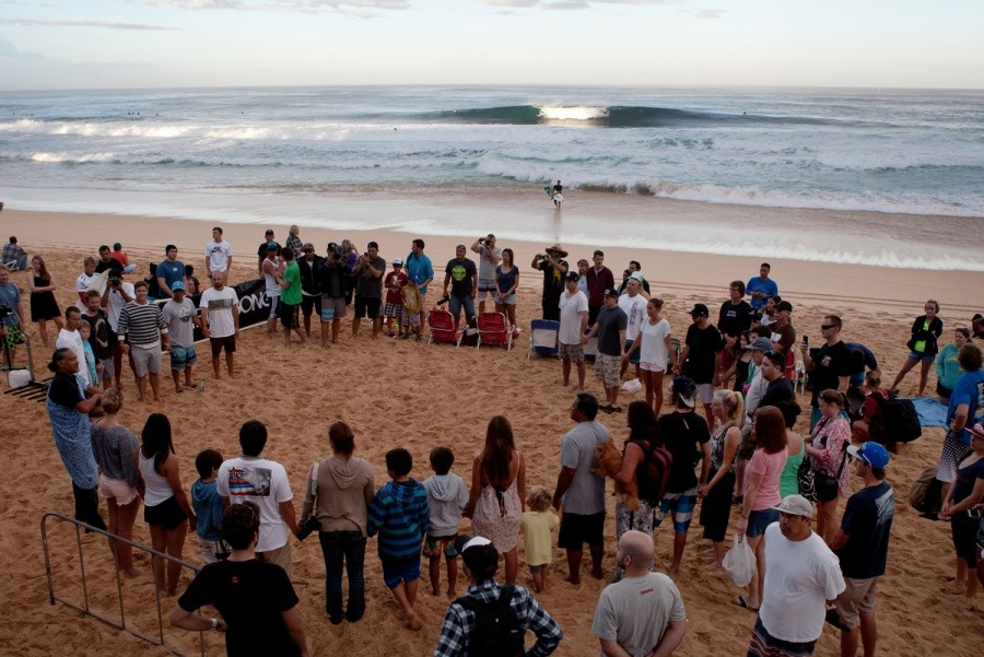 A perfect A-Frame peels through the lineup as the traditional Hawaiian blessing takes place before the start of the Billabong Pipe Masters.   © ASP / Cestari