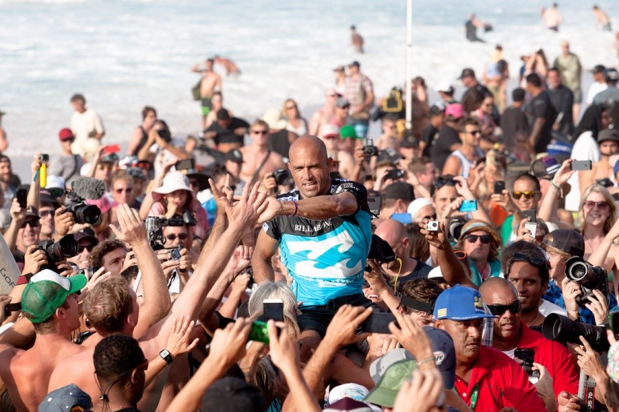 Kelly Slater (USA) is chaired up the beach as the 2013 Billabong Pipe Masters Champion.   © ASP / Cestari